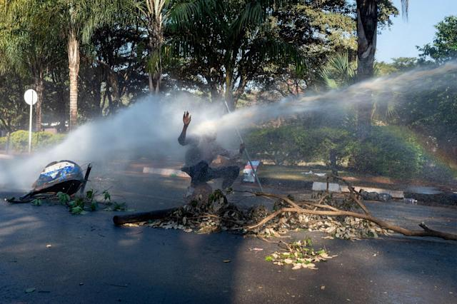 <p>A protester is hit in the face with a water cannon outside of the gates of the ZImbabwe Electoral Commission (ZEC) during a protest against polling results in Harare, Zimbabwe, 01 August 2018. The day saw protests turn violent when police fired rubber bullets and teargas, before the army was called in and began firing live rounds. (Photo: Yeshiel Panchia/EPA-EFE/REX/Shutterstock) </p>