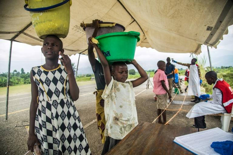Medical staff check people from the Democratic Republic of Congo, crossing into Uganda at a screening facility in Bundibugyo district, western Uganda -- but the Red Cross says its efforts to contain the disease can meet with distrust