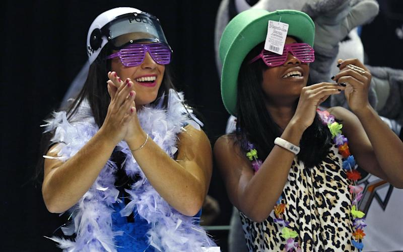 """Olympic gymnasts Aly Raisman, left, and Gabrielle Douglas dance the """"Harlem Shake"""" as athletes switch to their next rotation during the American Cup gymnastics competition in Worcester, Mass., Saturday, March 2, 2013. (AP Photo/Charles Krupa)"""