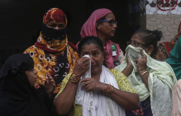 A woman wipes her tears after a three-story dilapidated building collapsed following heavy monsoon rains n Mumbai, India, Thursday, June 10, 2021. (AP Photo/Rafiq Maqbool)