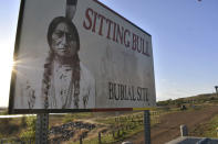 In this May 20, 2021, photo a banner for the burial site of Sitting Bull is seen in the Standing Rock Sioux Reservation in Fort Yates in North Dakota. The pipeline fight stirs bitter memories in Fawn Wasin Zi, a biology teacher who chairs the Standing Rock power authority. She grew up hearing her father and grandmother tell stories about a government water project that created Lake Oahe, how they had to leave their home then watch government agents burn it down, only to be denied housing, electricity and other promises of compensation. Wasin Zi, whose ancestors followed legendary Lakota Sioux leader Sitting Bull, now wants to ensure the tribe doesn't fall victim yet again to a changing world, where fossil fuels warm the planet and bring drought and wildfire. (AP Photo/Matt Brown)