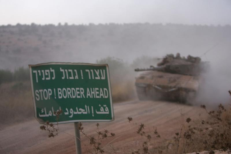 Israeli tanks are seen arriving at the Israel-Lebanon border, after returning from south Lebanon on August 16, 2006