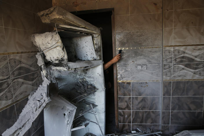 A local resident uses his mobile to take photos of the damages on a house, caused by a mortar fired from inside Syria, on the Turkish town of Akcakale, southeastern Turkey, Oct. 12, 2019. (Photo: Lefteris Pitarakis/AP)