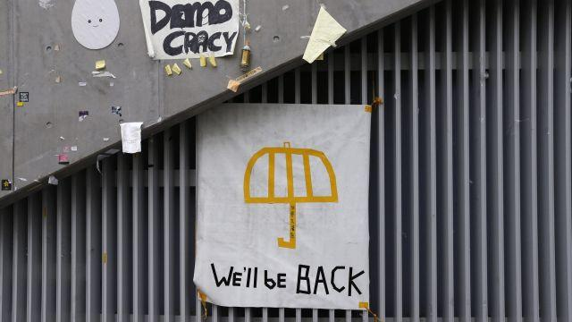 """A poster of an umbrella with the words """"We'll be back"""" written underneath is pictured on a wall at the main """"Occupy"""" protest site at Admiralty in Hong Kong"""