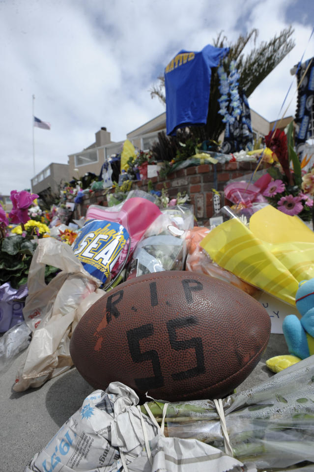 A football with Junior Seau's number sits in front of a memorial in the driveway of the house of former NFL star Junior Seau Thursday, May 3, 2012, in Oceanside, Calif. Seau's death in Oceanside, in northern San Diego County, stunned the region he represented with almost reckless abandon. (AP Photo/Denis Poroy)