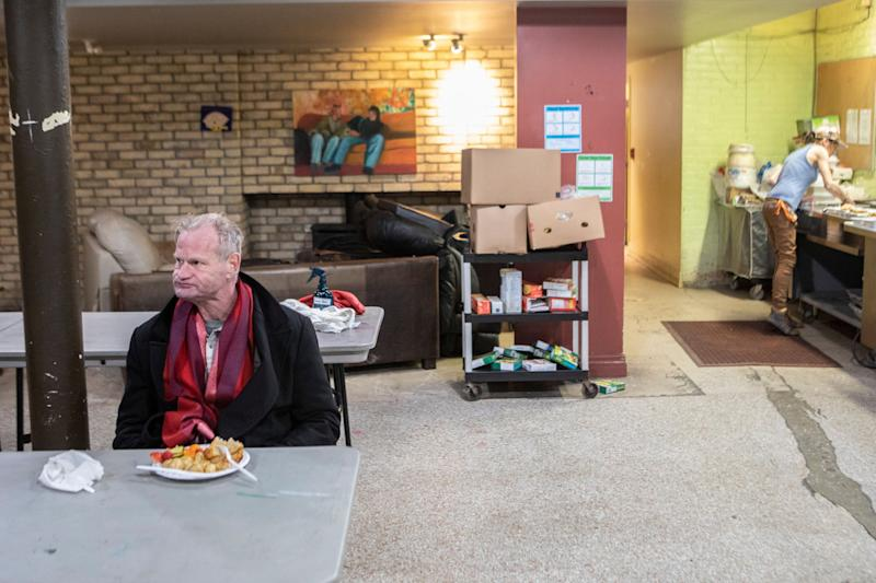 "A man sits for a meal served at The Sanctuary Drop-In Centre in Toronto on March 26, 2020. People who work with the city's homeless say more are on the streets because many drop-in and respite sites, have warned of an ""explosion"" of COVID-19 within within Toronto's homeless population. (Photo: Chris Young/CP)"