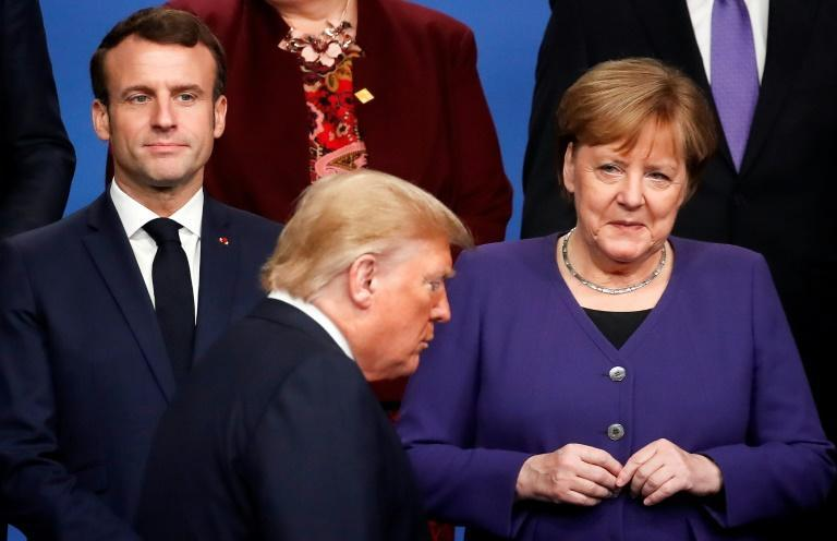 France's President Emmanuel Macron and Germany's Chancellor Angela Merkel, who have both butted heads with US President Donald Trump, watch him walk past as they pose for a photo at a NATO summit in Watford, England in December 2019