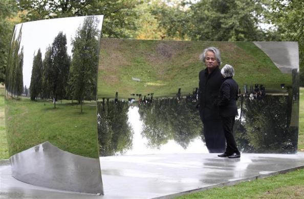 "Artist Anish Kapoor poses for a photograph in front of his work ""C-Curve"", part of his ""Turning the World Upside Down"" exhibition, in Hyde Park, central London September 27, 2010. REUTERS/Andrew Winning"