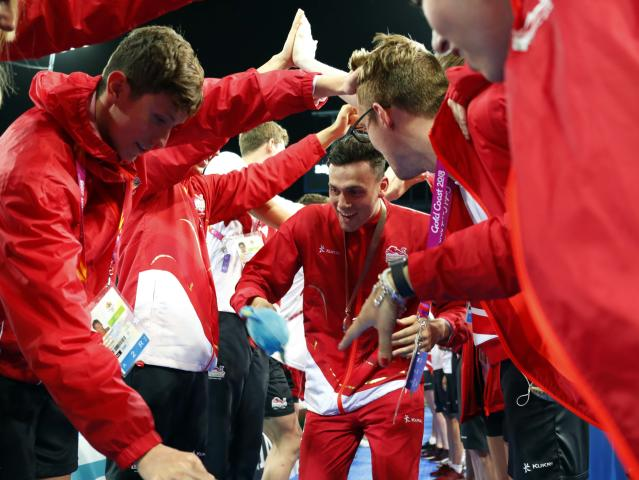 Swimming - Gold Coast 2018 Commonwealth Games - Men's 4x100m Medley Relay - Medal Ceremony - Optus Aquatic Centre - Gold Coast, Australia - April 10, 2018. James Guy of England walks as his team members form an archway. REUTERS/David Gray