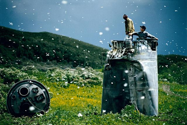 <p>Villagers collect scrap from a crashed spacecraft, surrounded by thousands of white butterflies in Altai Territory, Russia, 2000. Environmentalists fear for the region's future due to the toxic rocket fuel. (© Jonas Bendiksen/Magnum Photos) </p>