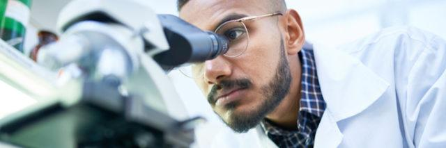 Portrait of young Middle-Eastern scientist looking in microscope while working on medical research in science laboratory, copy space (Portrait of young Middle-Eastern scientist looking in microscope while working on medical research in science laborat