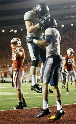 Utah State's Matt Austin is congratulated by Kellen Bartlett (81) after catching a touchdown pass during the first half of an NCAA college football game against Wisconsin Saturday, Sept. 15, 2012, in Madison, Wis. (AP Photo/Morry Gash)
