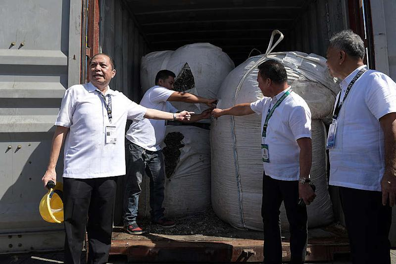 Bureau of Customs Port Collector John Simon opens a container van containing 22 sling bags of 2.561 tons of mixed electronic wastes before it will be sent back to Hong Kong at the Mindanao Container Port Terminal in Villanueva, Misamis Oriental. Photo: Froilan Gallardo/Greenpeace