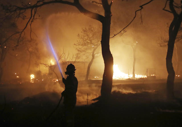 <p>A firefighter sprays water on the fire in the town of Mati, east of Athens, Monday, July 23, 2018. (Photo: Thanassis Stavrakis/AP) </p>