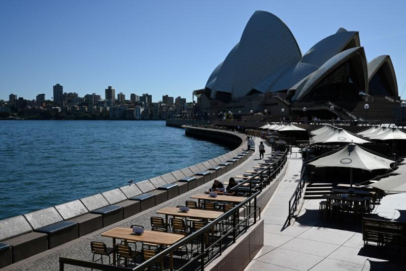 Tables at an open restaurant are seen mostly deserted on a quiet morning at the waterfront of the Sydney Opera House in Sydney
