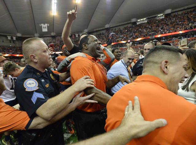 Syracuse head coach Dino Babers, center, celebrates a win over Clemson after the second half of an NCAA college football game, Friday, Oct. 13, 2017, in Syracuse, N.Y. Syracuse upset Clemson 27-24. (AP Photo/Adrian Kraus)
