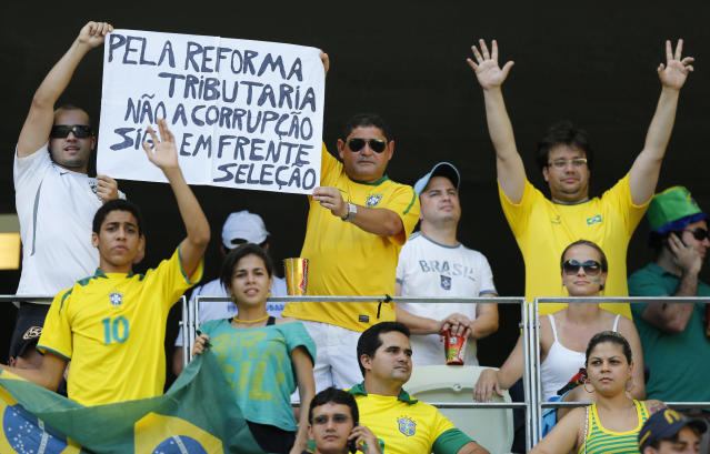 "Fans hold a sign ""Tribute to reform. No corruption. Go ahead Selecao"" prior to the soccer Confederations Cup group A match between Brazil and Mexico at Castelao stadium in Fortaleza, Brazil, Wednesday, June 19, 2013. (AP Photo/Fernando Llano)"