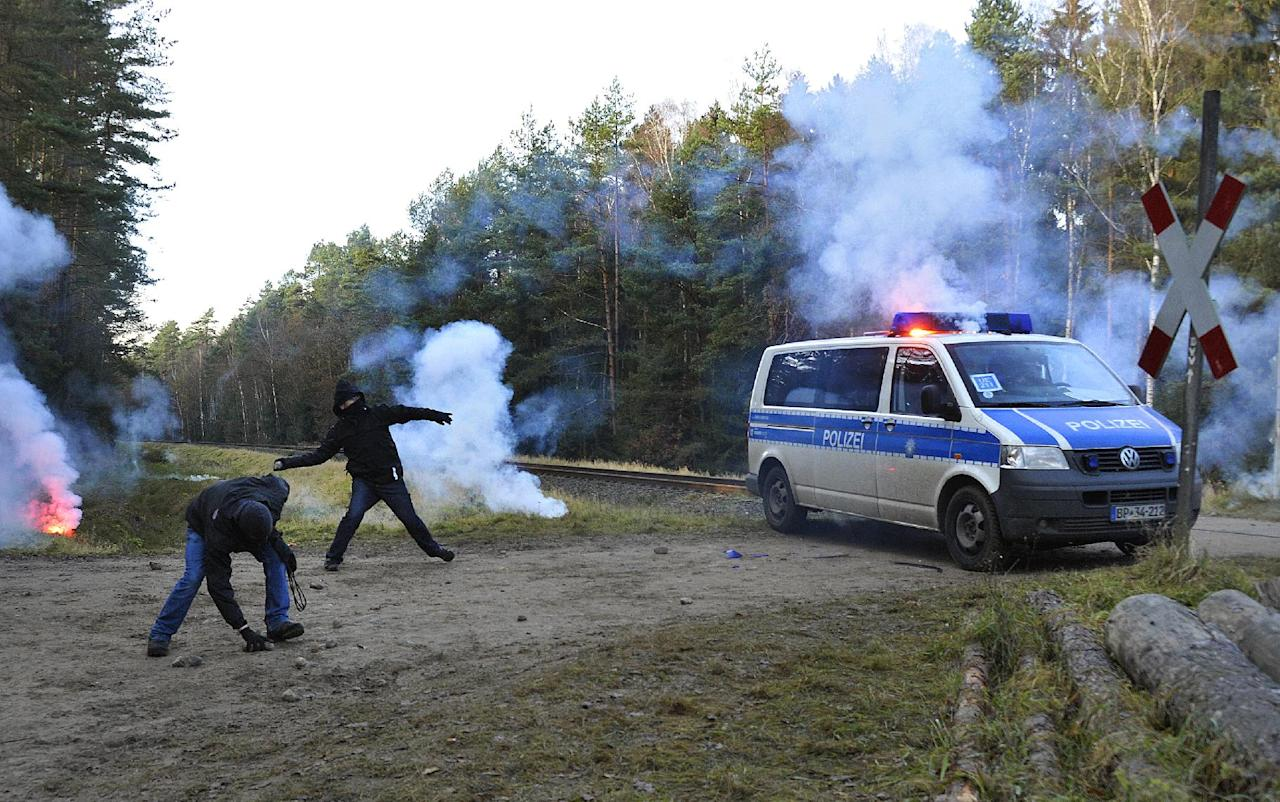 Violent environment activists attack a police car that stands next to the railroad track near Metzingen northern Germany Friday Nov. 25, 2011. A shipment of nuclear waste reprocessed in France crossed into Germany Friday on its way to a controversial storage site that protesters say is unsafe. The train carrying the annual shipment entered western Germany in the morning after delays in France, where activists damaged railtracks in an attempt to halt the cargo. It is the first such shipment from France to Germany since Berlin decided to shut all its nuclear plants by 2022, following the disaster at Japan's Fukushima plant. The transport is due to arrive at the storage site on Sunday. (AP Photo/dapd Sascha Schuermann)