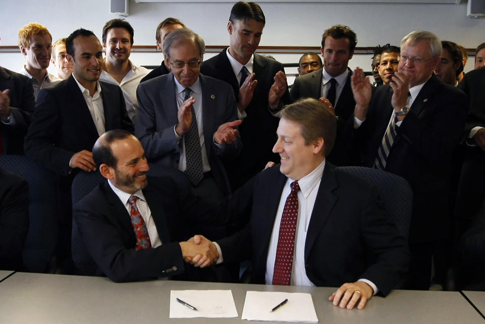 FILE - In this Saturday March 20, 2010, file photo, Major League Soccer commissioner Don Garber, left, shakes hands with MLS Players Association executive director Bob Foose after reaching an agreement on a contract in Washington. Major League Soccer has extended its deadline for negotiating adjustments to the existing collective bargaining agreement until Feb. 4, 2021, and warned it is prepared to lock out players if a deal isn't reached by then. (AP Photo/Luis M. Alvarez, File)