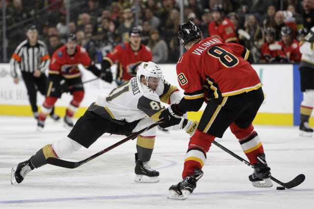 Vegas Golden Knights center Jonathan Marchessault (81) reaches for the puck against Calgary Flames defenseman Juuso Valimaki (8) during the second period of an NHL hockey game Friday, Nov. 23, 2018 in Las Vegas. (AP Photo/Joe Buglewicz)