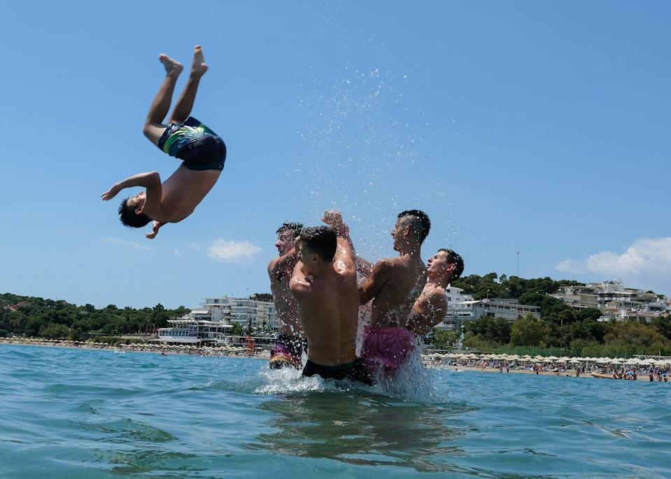 <p>People enjoy a day at Akti Vouliagmenis beach resort in Greece</p> (Getty Images)