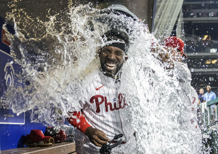 Philadelphia Phillies' Andrew McCutchen is dunked with water by Rhys Hoskins and Archie Bradley after hitting a three-run, walk-off home run in the ninth inning of a baseball game against the Washington Nationals, Monday, July 26, 2021, in Philadelphia. (AP Photo/Laurence Kesterson)