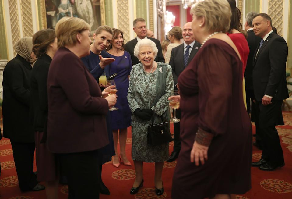 The Queen speaking to German Chancellor Angela Merkel (left) at the reception. (PA)