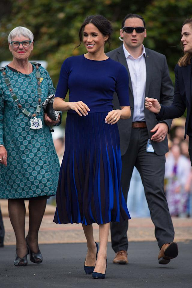 <p>The Duchess of Sussex wore a Givency bespoke navy pleated skirt teamed with a a navy crew neck blouse from the same designer label for a public walkabout. Photo: Getty </p>