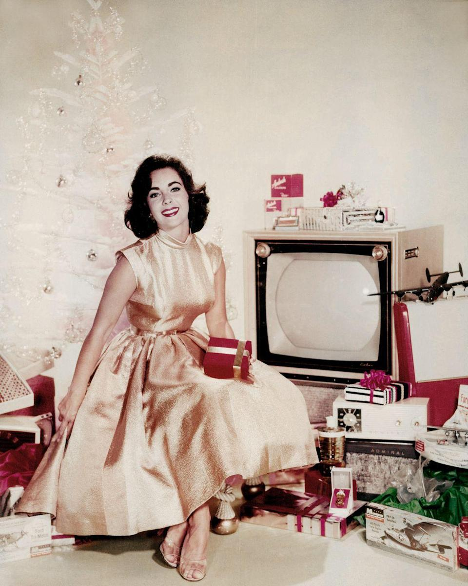 <p>The actress is the picture of Christmas in this 1955 advert, in which she poses next to a modern Christmas tree amongst dozens of presents. </p>