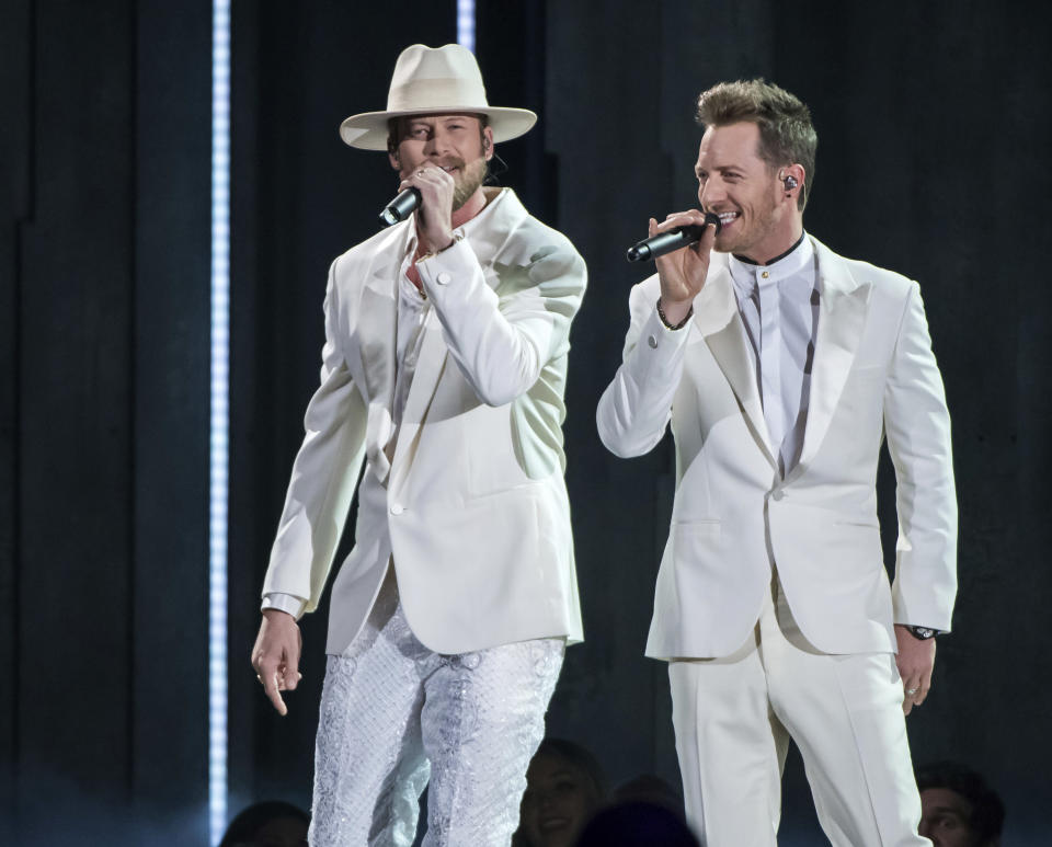 "FILE - Brian Kelley, left, and Tyler Hubbard of Florida Georgia Line perform ""Meant to Be"" at the 52nd annual CMA Awards in Nashville, Tenn. on Nov. 14, 2018. Hubbard is the second artist so far that will miss a scheduled performance at the CMA Awards on Wednesday due to COVID-19. He posted a note on his Instagram page on Monday, Nov. 9, 2020, saying he was asymptomatic and quarantining on his bus outside his home. It comes days after another artist, Lee Brice, also revealed he had tested positive and would not perform on the show. (Photo by Charles Sykes/Invision/AP, File)"
