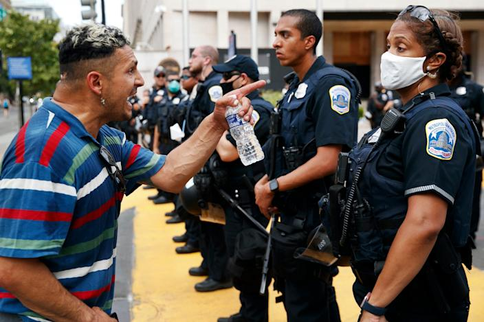 """A man is seen yelling at a Metropolitan Police officer in Washington, DC, during a George Floyd demonstration on June 23, 2020. <p class=""""copyright""""><a href=""""https://newsroom.ap.org/detail/RacialInjusticeWashington/e477db4eccc749ec96c1858433542bbd/photo?Query=black%20police%20officer%20protest&mediaType=photo&sortBy=arrivaldatetime:desc&dateRange=Anytime&totalCount=5341&currentItemNo=47"""" rel=""""nofollow noopener"""" target=""""_blank"""" data-ylk=""""slk:Jacquelyn Martin/AP"""" class=""""link rapid-noclick-resp"""">Jacquelyn Martin/AP</a></p>"""