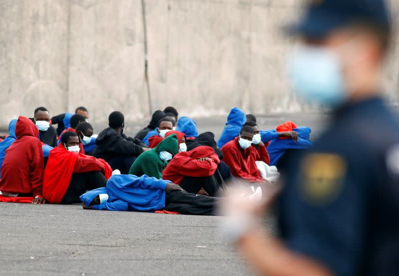 Migrants rescued in the Atlantic Ocean sit on the ground after disembarking from a Spanish coast guard vessel, in the port of Arguineguin