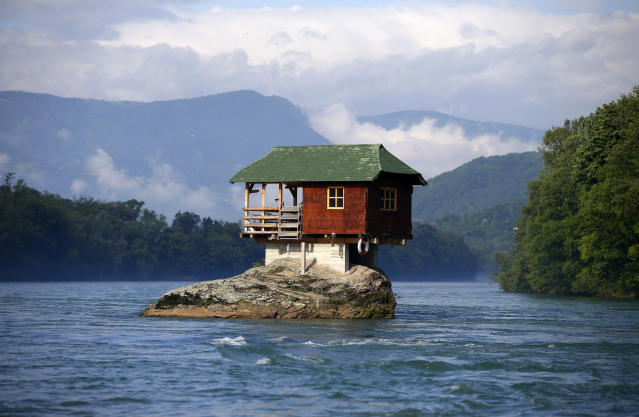 A house built on a rock on the river Drina is seen near the western Serbian town of Bajina Basta, about 160km (99 miles) from the capital Belgrade May 22, 2013. The house was built in 1968 by a group of young men who decided that the rock on the river was an ideal place for a tiny shelter, according to the house's co-owner, who was among those involved in its construction. REUTERS/Marko Djurica (SERBIA - Tags: ENVIRONMENT SOCIETY TRAVEL TPX IMAGES OF THE DAY) - RTXZWGT