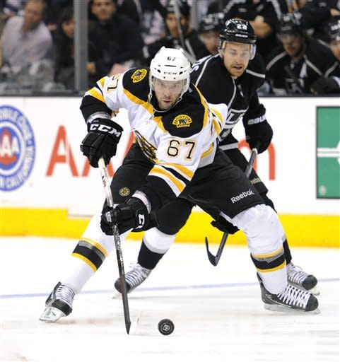 Boston Bruins left wing Benoit Pouliot (67) keeps the puck away from Los Angeles Kings center Trevor Lewis, back, in the first period of an NHL hockey game in Los Angeles, Saturday, March 24, 2012. (AP Photo/Lori Shepler)