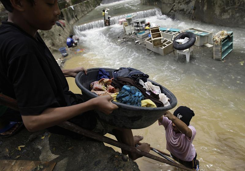 Residents clean their clothes along a river as floods recede in suburban Marikina city, east of Manila, Philippines, Friday Aug. 10, 2012. Philippine disaster officials were shifting Friday from rescue work to a massive clean-up of the capital following nonstop rains that left tons of muck and debris from floods littering the city. (AP Photo/Aaron Favila)