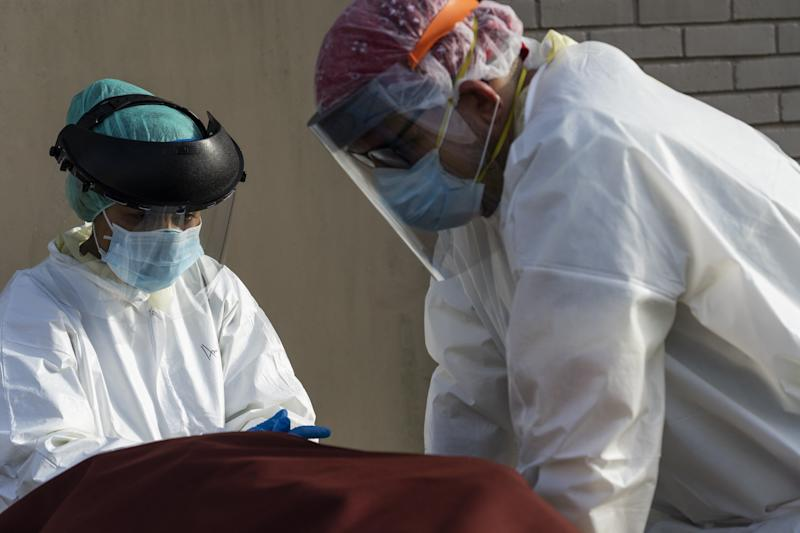 Medical staff wearing full PPE at a hospital in Houston, Texas wait for a car to pick up a body: Getty Images