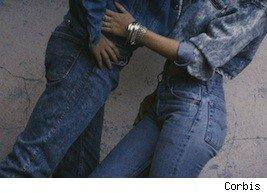 young people in jeans holding each other