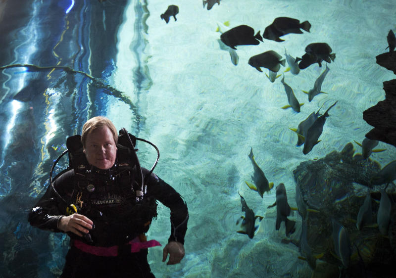 """In this photo taken on Saturday, July 28, 2012, American journalist and diving instructor Steven Schwankert in diving suit swims inside the Blue Zoo aquarium in Beijing. A lifelong scuba diving obsession led Schwankert to the tale of the HMS Poseidon and the startling discovery that the British submarine, which sank off the northeastern coast of China in the 1930s, had been raised by the Chinese in 1972. That revelation lies at the heart of Schwankert's upcoming book, """"The Real Poseidon Adventure: China's Secret Salvage of Britain's Lost Submarine"""" and an accompanying documentary film chronicling his search for answers about what became of the sunken vessel. (AP Photo/Andy Wong)"""
