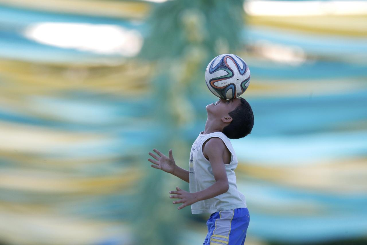 A boy play soccer with a Brazuca ball on a street decorated with references to the 2014 World Cup in the neighborhood of Ceilandia in Brasilia