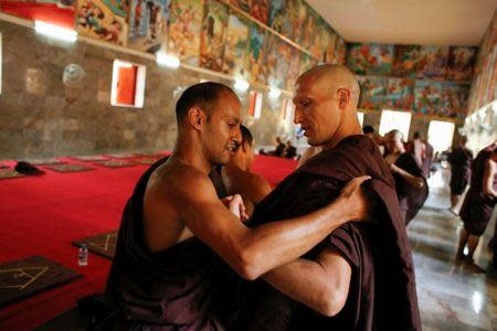 Monk Jeremy (L) helps Turkish-German patient Cengiz, now monk Atalo, to adjust his robes during his ordination ceremony at Wat Thamkrabok monastery in Saraburi province, Thailand, March 30, 2017. REUTERS/Jorge Silva