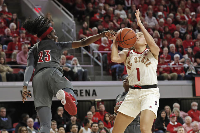 Louisville guard Jazmine Jones (23) blocks a shot attempt by North Carolina State guard Aislinn Konig (1) during the second half of an NCAA college basketball game in Raleigh, N.C., Thursday, Feb. 13, 2020. (AP Photo/Gerry Broome)