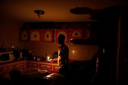 Americo Fernandez uses a candle to illuminate the kitchen at his home during a blackout in Maracaibo, Venezuela July 25, 2018. REUTERS/Marco Bello