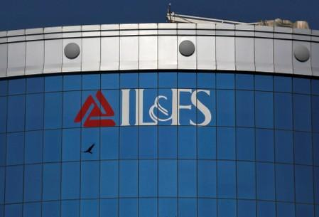 A bird flies next to the logo of IL&FS installed on the facade of a building at its headquarters in Mumbai