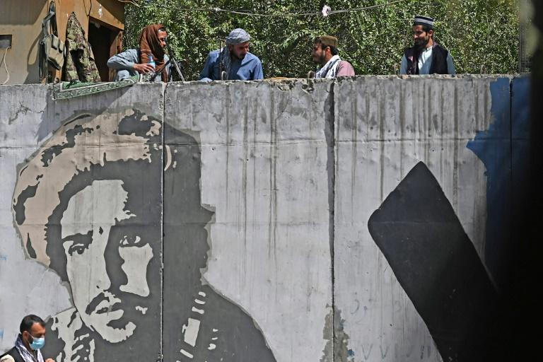 Taliban fighters by a concrete wall painted with an image of Ahmad Shah Massoud (AFP/Aamir QURESHI)