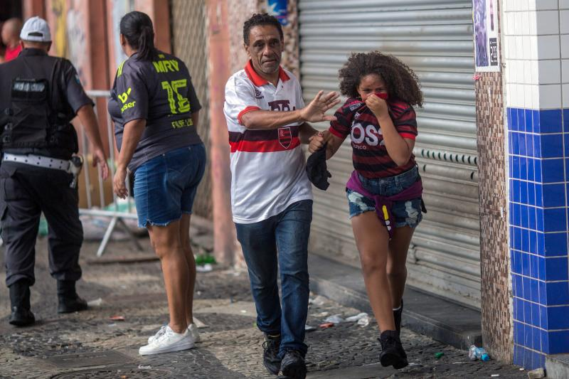 Fans of Flamengo football club taking part in a celebration parade, flee from tear gas shot by riot police after some alleged theft incidents within the crowd, in Rio de Janeiro, Brazil on November 24, 2019. (Photo by Daniel RAMALHO / AFP) (Photo by DANIEL RAMALHO/AFP via Getty Images)