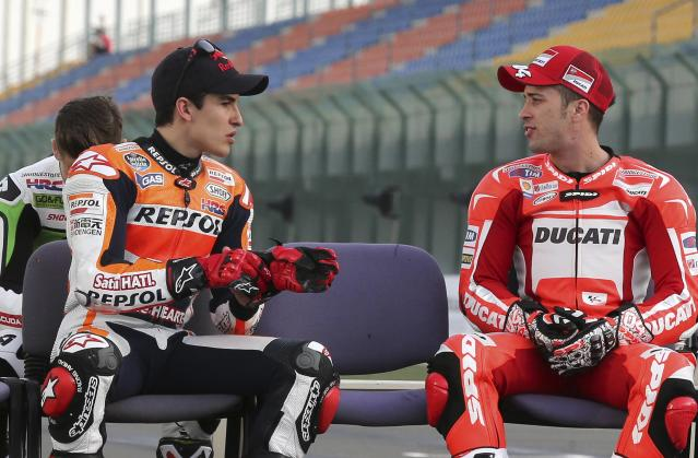 Ducati Team MotoGP rider Andrea Dovizioso (R) of Italy talks with Honda MotoGP rider Marc Marquez of Spain before the free practice session of the MotoGP World Championship at the Losail International circuit in Doha March 20, 2014. REUTERS/Fadi Al-Assaad (QATAR - Tags: SPORT MOTORSPORT)