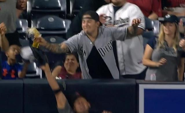 A Padres fan loses his beer but helps steal a home run for Eric Hosmer during Friday's game at Petco Park. (MLB.TV)