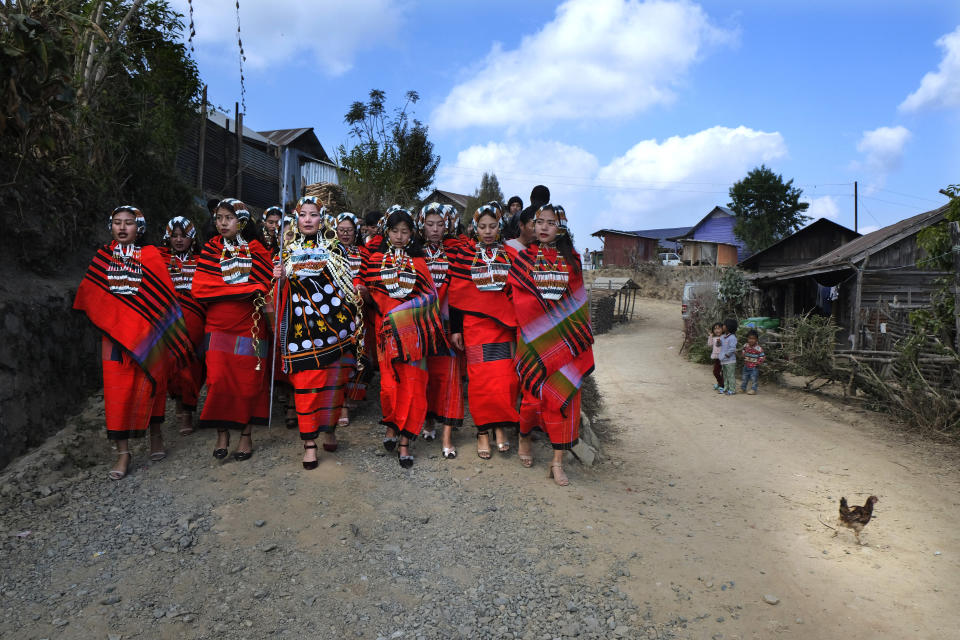 A group of Naga girls in traditional attire accompany a bride-to-be, center, as she leaves her village to travel to the village of her groom, in Shangshak village, in the northeastern Indian state of Manipur, Friday, Jan. 15, 2021. Nagas are an indigenous people living in several northeastern Indian states and across the border in Myanmar. (AP Photo/Yirmiyan Arthur)