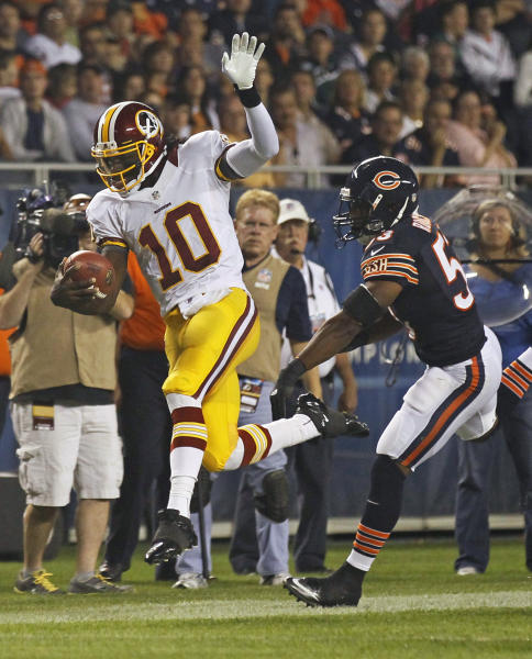 Washington Redskins quarterback Robert Griffin III (10) tries to stay in bounds as he is pursued by Chicago Bears linebacker Nick Roach (53) during the first half of an NFL preseason football game in Chicago, Saturday, Aug. 18, 2012. (AP Photo/Charles Rex Arbogast)