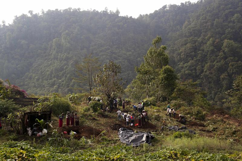 In this May 24, 2013 photo, Ixil gather around a mass grave as forensic anthropologists exhume the skeletons of their loved ones who died during the country's civil war, near Ixtupil, Guatemala. Forensic experts continue to exhume bodies from clandestine graves. Lesser known are the mass graves that the Ixil people themselves dug to bury loved ones who died of starvation and hypothermia, while they hid in the mountains from the soldiers who razed their villages and killed thousands. (AP Photo/Rodrigo Abd)